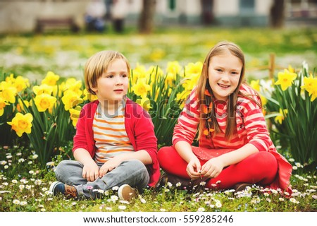 Two cute kids, little boy and his big sister, playing in the park between yellow daffodils flowers, wearing bright red clothes