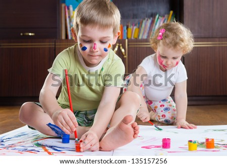 Two cute kids painting with colorful paints
