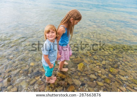 Two cute kids playing in the lake - stock photo