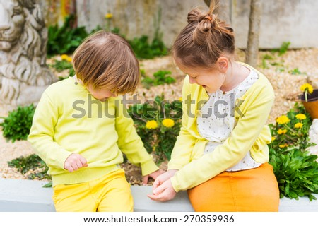 Two cute kids playing outdoors, wearing yellow clothes - stock photo