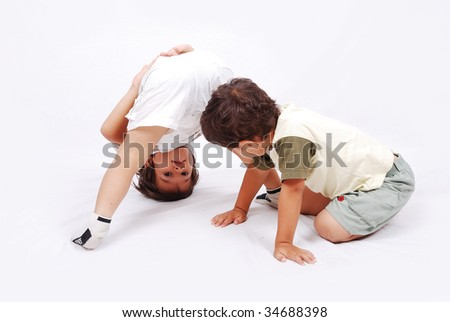 Two cute kids playing together isolated in white - stock photo