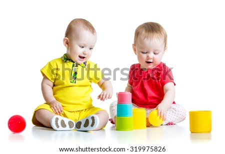 Two cute kids playing with cup toys. Toddlers girl and boy sitting on floor, isolated on white background. - stock photo