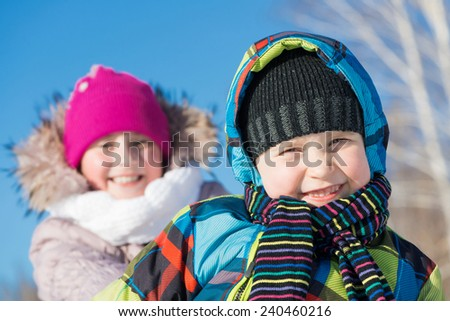 Two cute kids riding sled and having fun - stock photo