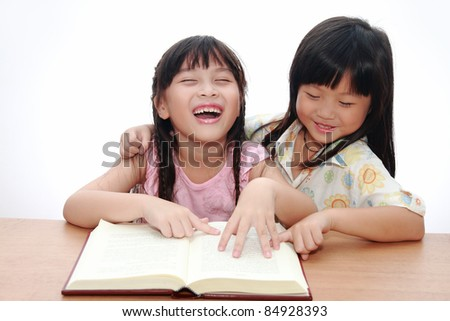 Two Cute little asian girl happy reading book - stock photo