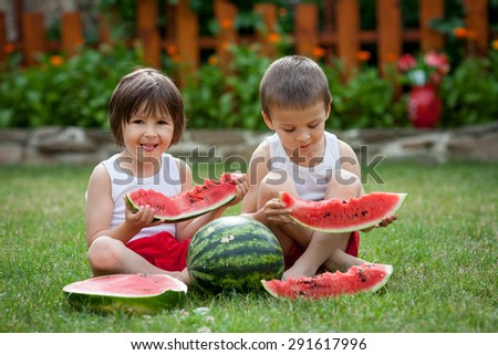 Two cute little boys, eating watermelon in the garden, summertime
