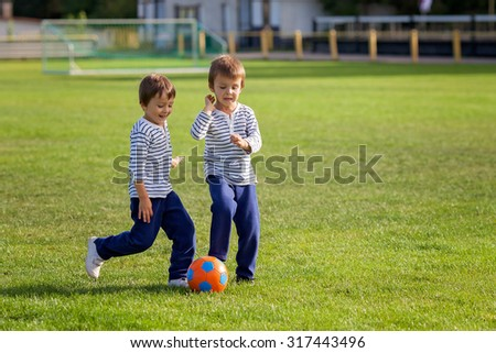 Two cute little boys, playing football outdoor, autumn time