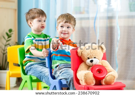 Two cute little boys playing role game in daycare - stock photo