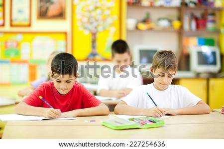 Two cute little boys sitting in the classroom and writing. Elementary age. Other kids in the background. NOTE: All the drawings and artwork in the classroom are made by children. - stock photo