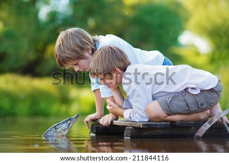 "Two cute little boys sitting on a wooden bridge and looking at the magic pike in a sunny summer day. Russian folk take ""By a wave of the wand"". Kids are playing. - stock photo"