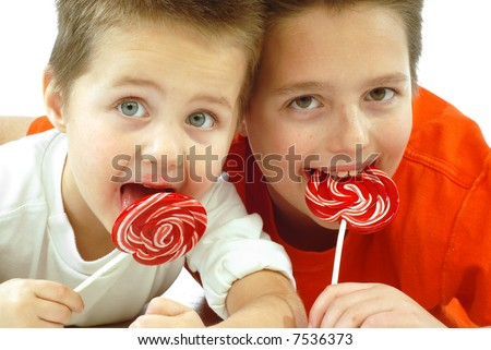 Two cute little brothers enjoying candy together; isolated on white - stock photo