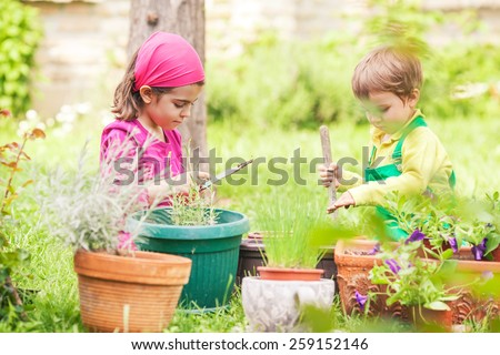 Two cute little children gardening in front or back yard - stock photo