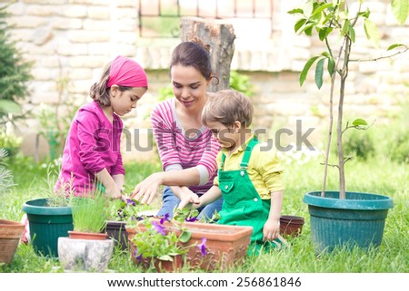 Two cute little children helping their mother gardening - stock photo
