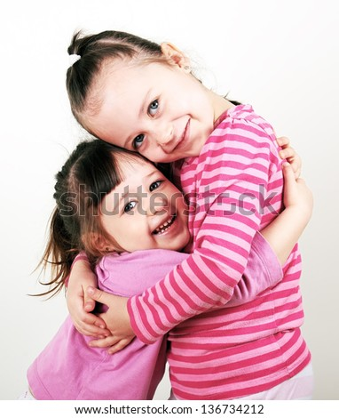 Two cute little girls are playing together, isolated on white background - stock photo