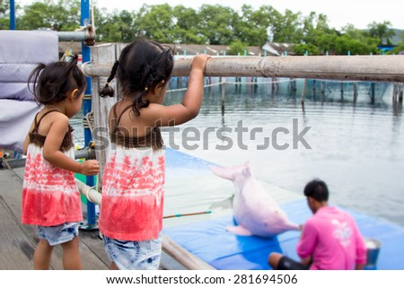 Two cute little girls having fun to look pink dolphin feeding in the oasis sea world Thailand - stock photo