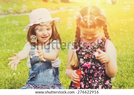 Two cute little girls on picnic in park on sunny summer day. Little sisters playing with water balloons outdoors in nature. Horizontal, retouched, filter, vibrant colors. - stock photo