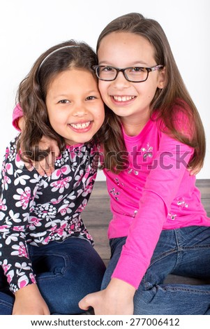 Two cute little girls sitting on the floor together - stock photo