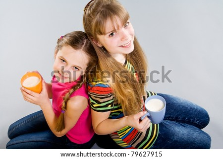 Two cute little girls with colorful mugs - stock photo