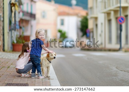 Two cute little sisters and a dog in italian town - stock photo