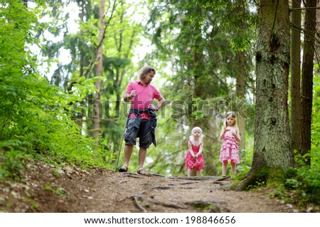 Two cute little sisters and their father outdoors at summer