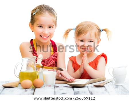 two cute little sisters cooking isolated on a white background - stock photo