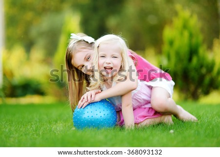 Two cute little sisters having fun together on the grass on a sunny summer day - stock photo