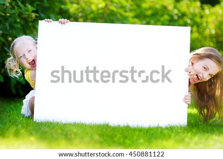 Two cute little sisters holding big blank whiteboard on warm and sunny summer day outdoors