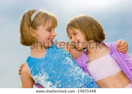 Two cute little sisters over blue sky - stock photo