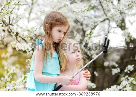 Two cute little sisters taking a photo of themself with a selfie stick on beautiful summer day - stock photo