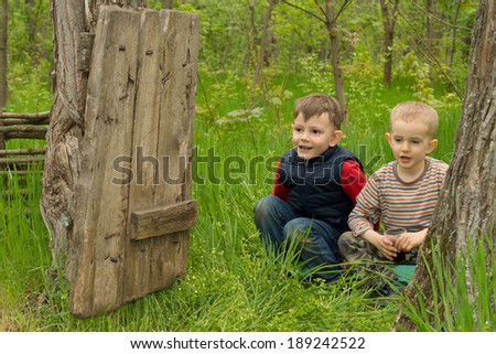 Two cute playful young boys squatting down in the long green grass looking through an open dilapidated old wooden gate between two trees in woodland grinning with happiness as they enjoy the outdoors - stock photo