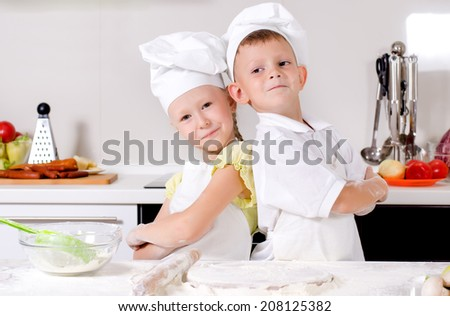 Two cute proud young chefs with a little boy and girl standing back to back in the kitchen in their white uniforms and toques with folded arms smiling at the camera - stock photo