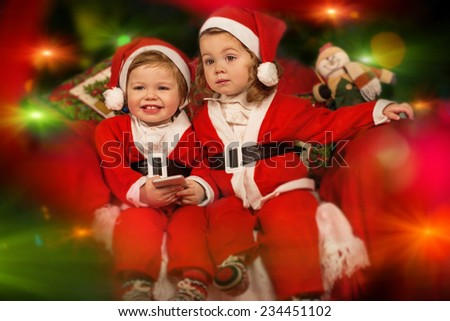 two cute santa's helpers with phone  - stock photo