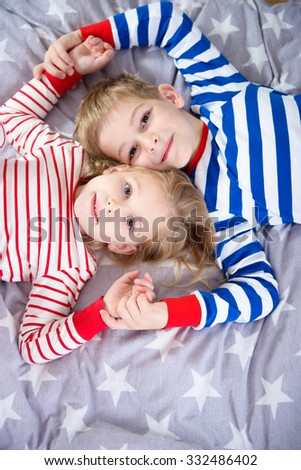 Two cute siblings lying in sleepwear on bed. View from above