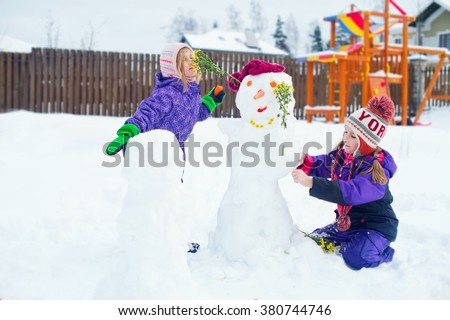 Two cute sisters building snowman with carrot nose and flowers in hands on back yard of house - stock photo
