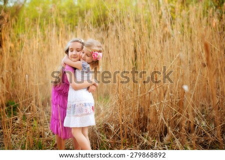 Two cute sisters girls holding each other tight with love in field of yellow dry grass - stock photo