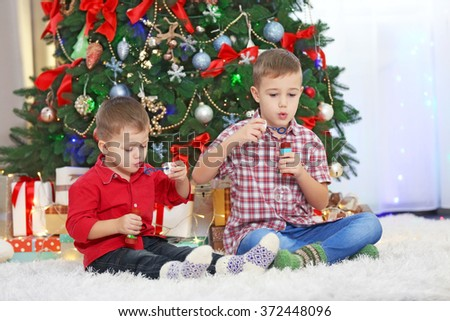 Two cute small brothers blows soap bubbles on Christmas tree background - stock photo