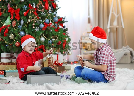 Two cute small brothers opening gifts on Christmas decoration background