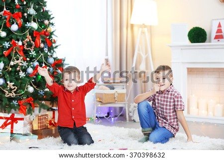Two cute small happy brothers on Christmas tree background - stock photo