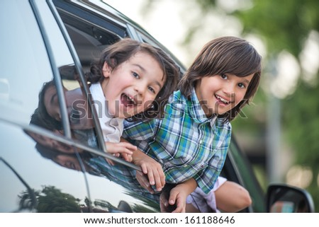 Two cute smiling kids looking out from car window - stock photo