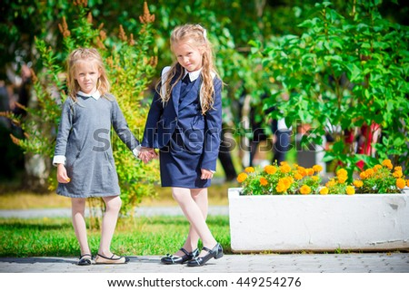 Two cute smilling little girls posing in front of their school. Adorable little kids feeling very excited about going back to school - stock photo