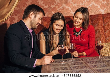 two cute women and a man sitting in  restaurant  use the phone