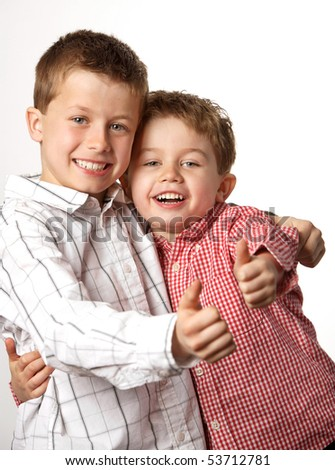 two cute young boys arm in arm with thumbs up - stock photo