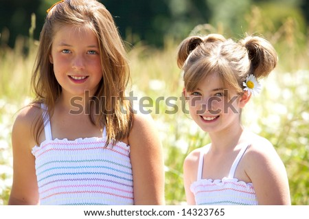 Two cute young girls in matching dresses - stock photo