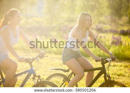 Two cute young happy smiling beautiful women girlfriends wearing jeans shorts riding bikes in park in bright sunlight on summer day - stock photo