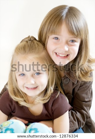 Two cute young sisters posing together in a studio. Vertically framed shot isolated against a white studio background. The older sister is hugging the younger one. Both are smiling at the camera