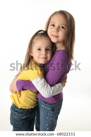 Two cute young sisters standing up hugging each other, isolated on white - stock photo