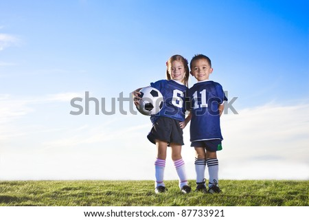Two cute youth soccer players wearing their team uniforms - stock photo