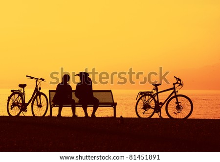 Two cyclist sitting relaxing by the beach - stock photo