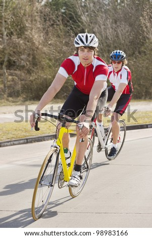 Two cyclists follwing eachother through a curve in the road - stock photo