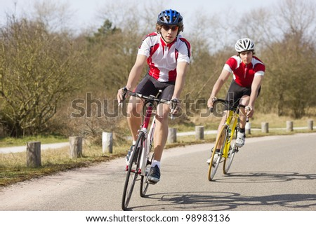 Two cyclists leaning inwards in the curve of a road during a training tour on a sunny spring day - stock photo