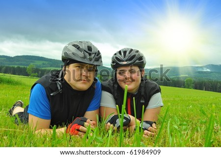 two cyclists on green meadow